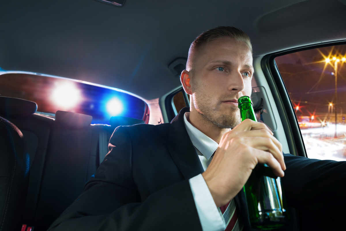 business man getting pulled over for drinking and driving with beer in hand