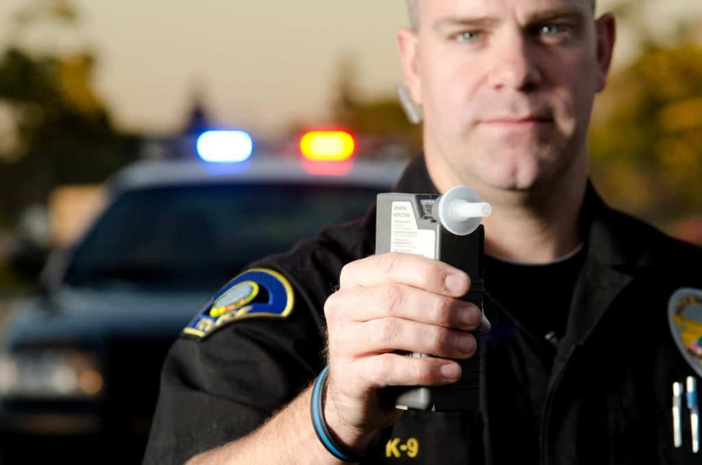 cop holding breathalyzer machine