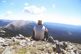 Man sitting on mountain reflecting on life